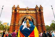 "Supporters of an independence for Catalonia listen to Catalan president Carles Puigdemont's speech broadcasted on a television screen at the Arc de Triomf (Triumphal Arch) in Barcelona on October 10, 2017. Catalonia's leader Carles Puigdemont said Tuesday he accepted the ""mandate of the people"" for the region to become ""an independent republic,"" but proposed suspending its immediate implementation to allow for dialogue.  10, 2017 in Barcelona, Spain. Christian Mantuano / OneShot"