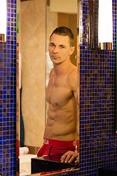 shirtless muscular man in a bathroom mirror