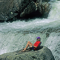 A hiker relaxes beside Crazy Creek in Wyoming's Beartooth Mountains.