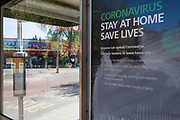 At the beginning of the fourth week of the UK government's lockdown during the Coronavirus pandemic, and with 120,067 UK reported cases with 16,060 deaths, a bus remains stationary in front of a deserted bus shelter displaying a 'Stay At Home', 'Save Lives' poster, at Waterloo bus station in South London, on 20th April 2020, in London, England.
