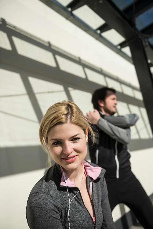 Man and woman in sportswear doing stretching