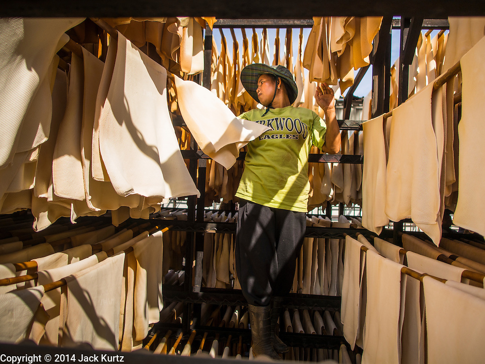 """16 DECEMBER 2014 - CHUM SAENG, RAYONG, THAILAND: A worker hangs rubber sheets to dry before they are put into a smoker at a large rubber plantation near Chum Saeng, Thailand. Thailand is the second leading rubber exporter in the world. In the last two years, the price paid to rubber farmers has plunged from approximately 190 Baht per kilo (about $6.10 US) to 45 Baht per kilo (about $1.20 US). It costs about 65 Baht per kilo to produce rubber ($2.05 US). Prices have plunged 5 percent since September, when rubber was about 52Baht per kilo. Some rubber farmers have taken jobs in the construction trade or in Bangkok to provide for their families during the slump. The Thai government recently announced a """"Rubber Fund"""" to assist small farm owners but said prices won't rebound until production is cut and world demand for rubber picks up.    PHOTO BY JACK KURTZ"""