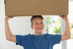 Young boy carrying box new apartment