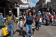 With many people and families staying in the UK for their Summer break during the school holidays, a large number of domestic tourists, who may normally have been travelling abroad, have decended on the capital to see the sights, as seen here in Leicester Square on 10th August 2021 in London, United Kingdom. Following the Coronavirus / Covid-19 health scare of the last two years, and with some travel restrictions still in place, more people have chosen a staycation which is a holiday spent in ones home country rather than abroad, or one spent at home and involving day trips to local attractions.
