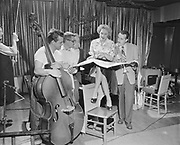 """Y-560104B-1. """"Christine Jorgensen at Sorrentos. January 4, 1956""""  """"Christine Jorgensen, the ex-GI who wanted to become  woman, opened in a comedy song act at Sorrento's Wednesday night. Here at rehersal, she talks over music with musicians Warren Black, left, Jack Parker, Eddie Wied and Don Fowler"""" caption published in Oregonian, January 5, 1956, pg. 11."""