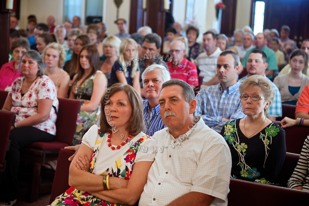 People are listening to Curtis Hice, 27, while singing at his community church service in Winchester, Tennessee, where he works at Social Security office. He lives with his wife and 2-year-old daughter. Curtis was a Marine combat engineer and fought during the first battle for Fallujah. After returning to the USA, he became more devoted and turned into religion. He is now the solo singer at his community church..