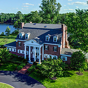 A real estate marketing image of the main house at Three Rivers Farm, with the river visible in the background. Taken for the agent.