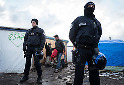 © London News Pictures. Calais, France. 07/03/16. Riot police stand guard as an Eritrean man leaves his shelter with only a sleeping bag. French authorities are evicting and demolishing the southern half of the Calais 'Jungle' camp, which charities estimate to contain 3,500 people. . Photo credit: Rob Pinney/LNP