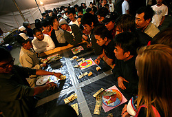 03 Feb 2006. East New Orleans, Louisiana. <br /> Tet, or Tet Nguyen Dan, Vietnamese Lunar New Year. Year of the Dog celebrations amongst the Vietnamese community of East Orleans. Gamblers exchange cash and smiles playing a dice game amidst furious scenes in a mini Vietnamese 'casino' where proceeds allegedly go to the church to aid in the rebuilding of the area and the creation of an elderly retirement home in the community.<br /> Photo; Charlie Varley/varleypix.com