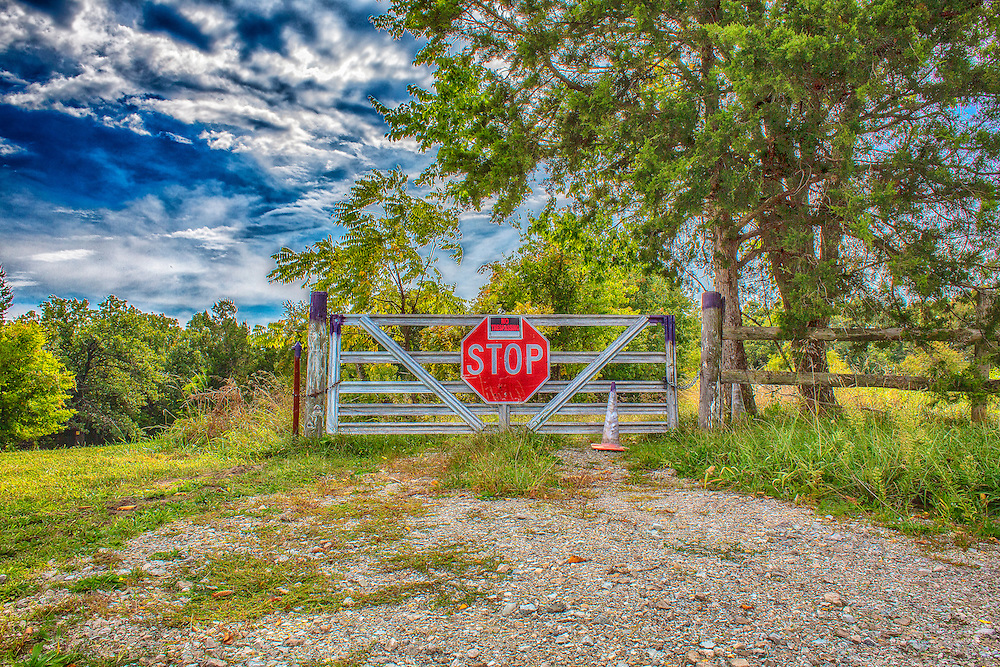 This is when stop means I have to go now to see whats on the other side of the fence. It may not be greener but I have to see for myself. No Trespassing and Stop signs simply mean further exploration is needed to a photographer.