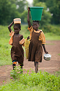 Girls carrying water, pots and schoolbooks walk to school near the Anglican Primary School in the Savelugu-Nanton district, northern Ghana on Wednesday June 6, 2007.