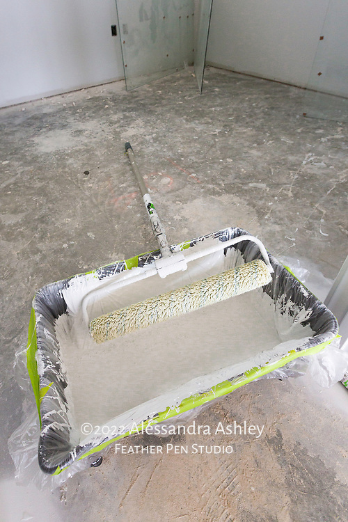 Large paint roller prepared with primer as painting begins at building site of new physical therapy and wellness center.