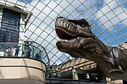 In Trinity Shopping Centre, one man in a group of people takes a picture of a roaring animatronic T-Rex dinosaur, part of Leeds Jurassic Trail school holiday event, using his smart phone on 8th August, 2021 in Leeds, United Kingdom. The Jurassic Trail is an event in Leeds that, until mid-September, will invite people to find 13 animatronic dinosaurs scattered throughout the city.