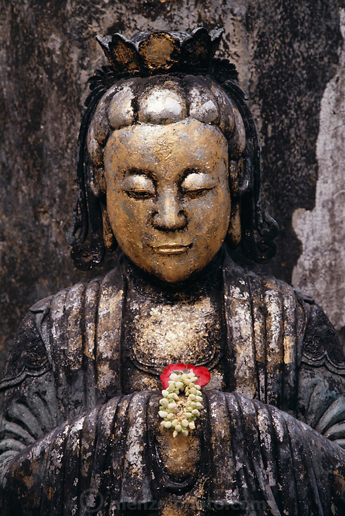 The lives of the majority of Thai people are dominated by traditional agricultural rhythms and the sounds of Buddhist rituals at the nearby temple. In homes across the country the most important image is Buddha. The image shown here is a bas-relief of Buddha at the Grand Palace in Bangkok, Thailand. Published in Material World page 83.