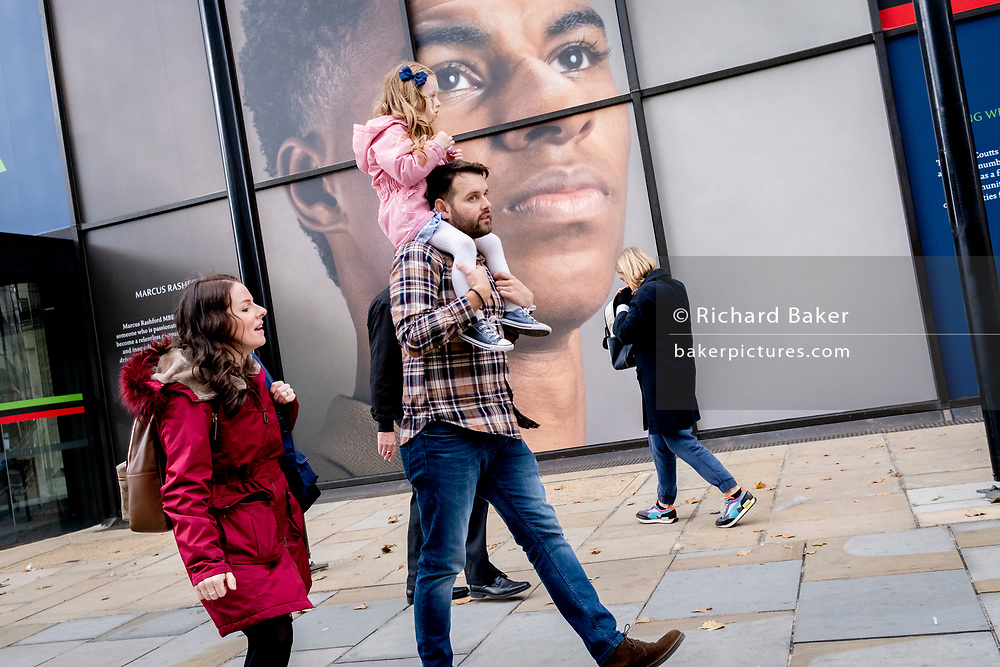 A young girl and some adults walk beneath the large billboard, a portrait of English football player, Marcus Rashford, outsidee the Strand branch of Coutts Bank, on 14th October, 2021, in Westminster, London, England. Marcus Rashford has recently been awarded an honourary degree by The University of Manchester in recognition of his political campaigning on behalf of the underprivilged (in particular, of school meals) and his philanthropy. He currently plays for Manchester United and is in the English national team. He has also been the victim of online racial abuse.