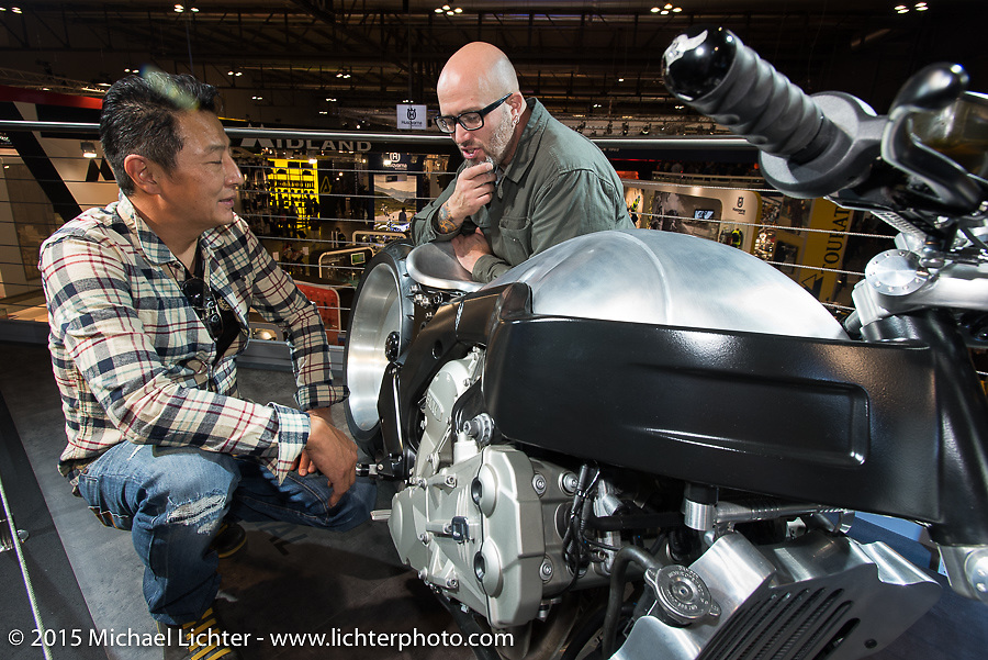 Custom bike builder Ken Nagai of Ken's Factory in Tokyo with his BMW custom commission at BMW head of design Ola Stenegard at EICMA, the largest international motorcycle exhibition in the world. Milan, Italy. November 17, 2015.  Photography ©2015 Michael Lichter.