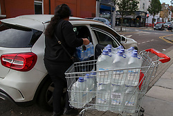 © Licensed to London News Pictures. 07/10/2020. London, UK. A shopper puts the cases of drinking water bottles in her car as homes in East London are still without water following a water main pipe burst in Hackney Marshes on Tuesday. Photo credit: Dinendra Haria/LNP