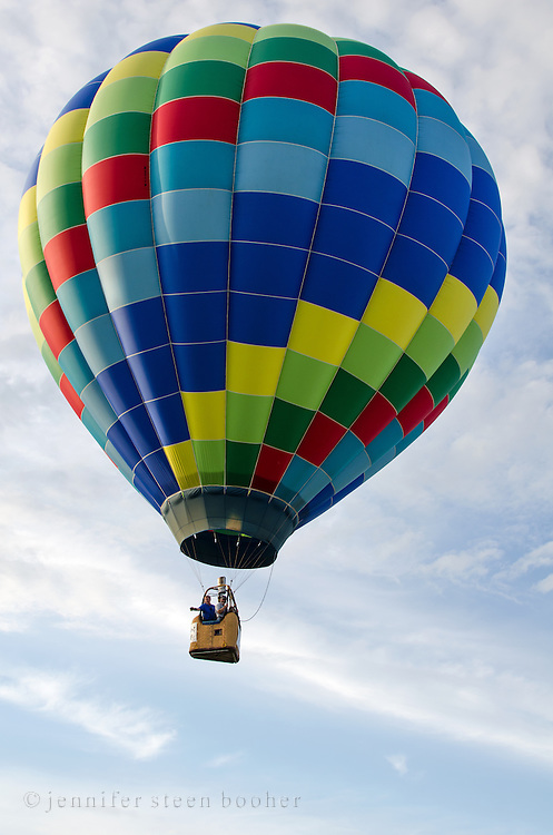 The rainbow-colored 'Tracer' drifts through white clouds in a blue sky, Crown of Maine Balloon Fair, Presque Isle, Maine.