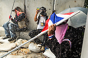 01 DECEMBER 2013 - BANGKOK, THAILAND: Thai anti-government protestors take shelter, including under a Thai flag, while chemical dispersal agents rain down on them. Thousands of anti-government Thais confronted riot police at Phanitchayakan Intersection, where Rama Vand Phitsanoluk Roads intersect, next to Government House (the office of the Prime Minister). Protestors threw rocks, cherry bombs, small explosives and Molotov cocktails at police who responded with waves of tear gas and chemical dispersal weapons. At least four people were killed at a university in suburban Bangkok when gangs of pro-government and anti-government demonstrators clashed. This is the most serious political violence in Thailand since 2010.    PHOTO BY JACK KURTZ