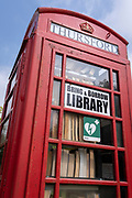 The former phone kiosk that now serves the local village community with a bring and borrow book library service, on a viillage green in rural Norfolk, on 27th June 2021, in Thursford, Norfolk, England.