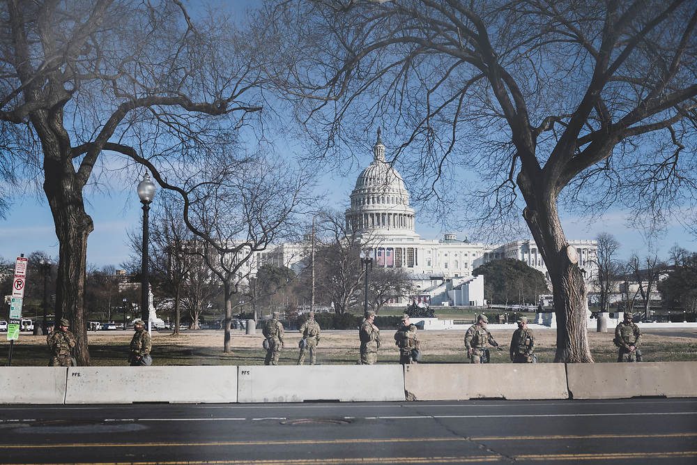 Washington DC, USA - January 21, 2021: View through the fence surrounding the Capitol Building of National Guard troops the day after the Biden inauguration.