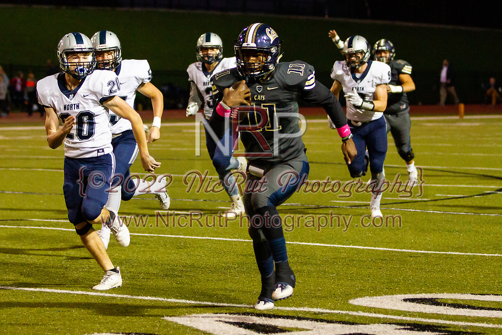 Southmoore's Jaedyn Scott running past Edmond North's Preston Smith for a gain of yards during the game on , Friday, October 19, 2018, at Moore Stadium.