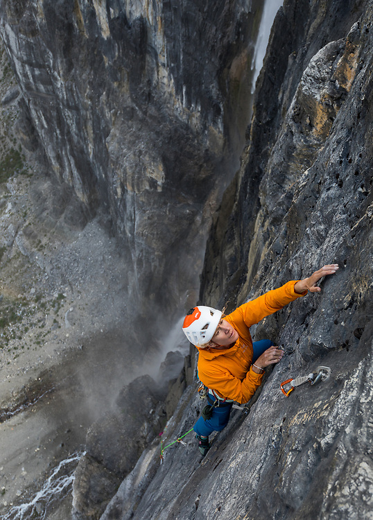 Sarah Hueniken climbing the last pitch of Arch Enemy, 7 pitches 5.11d, beside the raging waterfall Nemesis in Kootenay National Park at the Stanley Glacier Headwall.