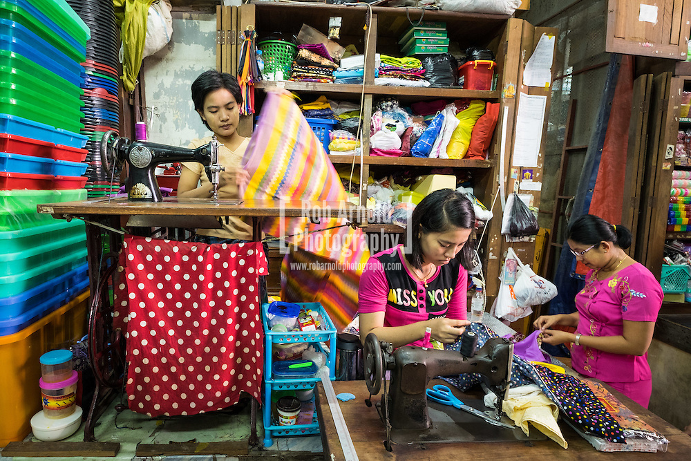 A woman makes adjustments to a colourful Longyi (traditional Myanmar dress) in Theingyi Market in Downtown Yangon.