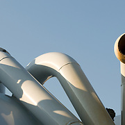 three white pipes with blue sky in the background