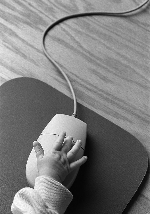 Black and white photo of baby's hand on a computer mouse