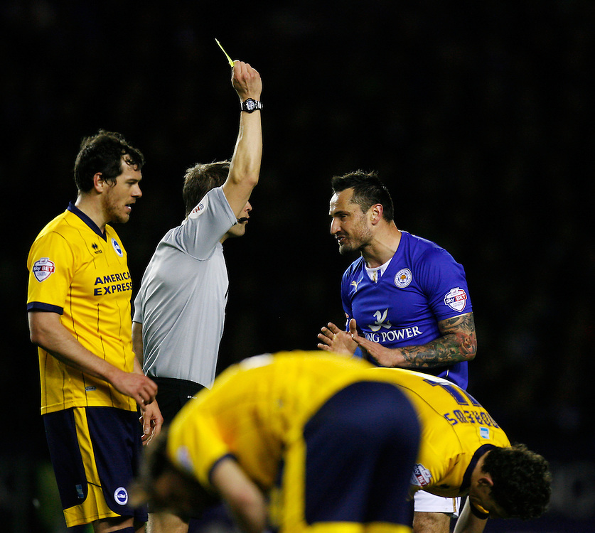 Leicester City's Marcin Wasilewski (R) is shown a yellow card by referee Craig Pawson <br /> <br /> Photo by Jack Phillips/CameraSport<br /> <br /> Football - The Football League Sky Bet Championship  - Leicester City v Brighton and Hove Albion - Tuesday 8th April 2014 - King Power Stadium - Leicester<br /> <br /> © CameraSport - 43 Linden Ave. Countesthorpe. Leicester. England. LE8 5PG - Tel: +44 (0) 116 277 4147 - admin@camerasport.com - www.camerasport.com