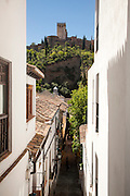 Narrow alleyway in the Moorish housing district of Albaicin, Granada, Spain with a view to the Alhambra