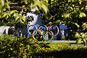 Visitors pose for pictures with the Olympic Rings at the Japan Olympic museum outside the Olympic Stadium, main venue of the Tokyo 2020 Olympic Games, in Tokyo on August 5, 2021. (Photo by Yuki IWAMURA / AFP)