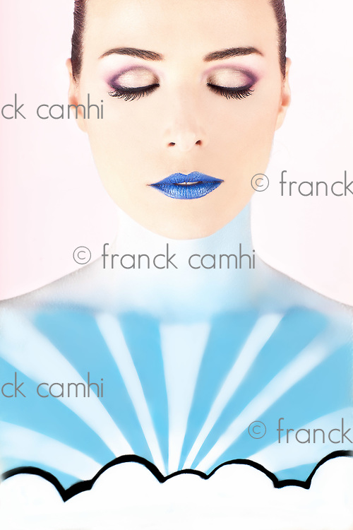 Closeup portrait of an artistic woman painted with blue representing the sky isolated on pink background