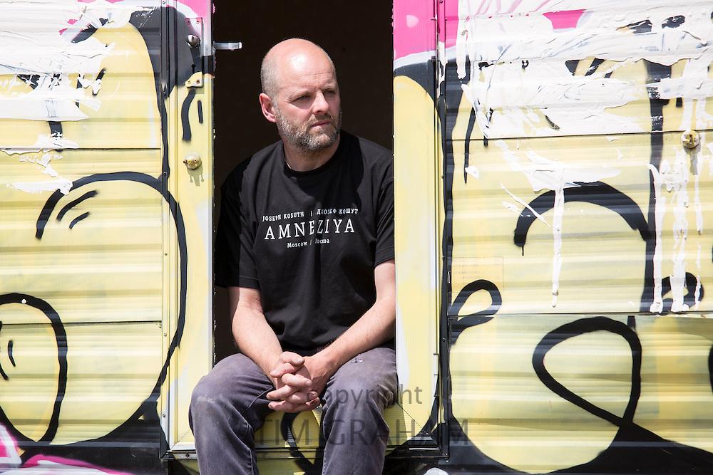 Gavin Turk, artist, photographed with a caravan (not his artwork) on wasteland near his East London studio, UK