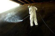 pvcBIRDPOOPER1/10-24-07/ASEC.  James Valencia (CQ), who works with the city's solid waste department, wears protective clothing while using a power washer to blast away bird droppings beneath the I-25 overpass at Coal, photographed Wed. Oct. 24, 2007.  (Pat Vasquez-Cunningham/Journal)