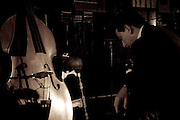 This photograph taken at Ortliebs's Jazz & Blues Club in Center City, Philadelphia. Man in front of his acoustic bass that is leaned against a barstool. Light is reflecting off of the acoustic bass.