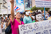 """09 JUNE 2013 - BANGKOK, THAILAND:   Anti-government protester on the plaza in front of Central World in Bangkok. The White Mask protesters wear the Guy Fawkes mask popularized by the movie """"V for Vendetta"""" and the protest groups Anonymous and Occupy. Several hundred members of the White Mask movement gathered on the plaza in front of Central World, a large shopping complex at the Ratchaprasong Intersection in Bangkok, to protest against the government of Thai Prime Minister Yingluck Shinawatra. They say that her government is corrupt and is a """"puppet"""" of ousted (and exiled) former PM Thaksin Shinawatra. Thaksin is Yingluck's brother. She was elected in 2011 when her brother endorsed her.   PHOTO BY JACK KURTZ"""