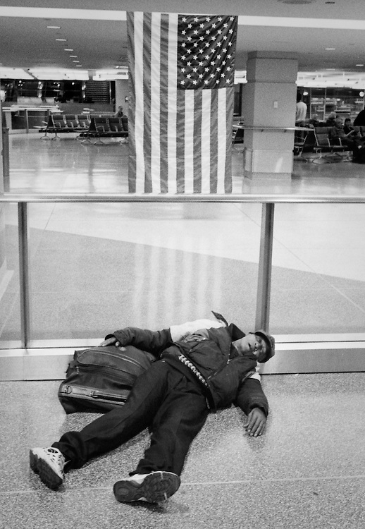 A passenger sleeps on New York's Penn Station floor, while awaiting a train from the city.