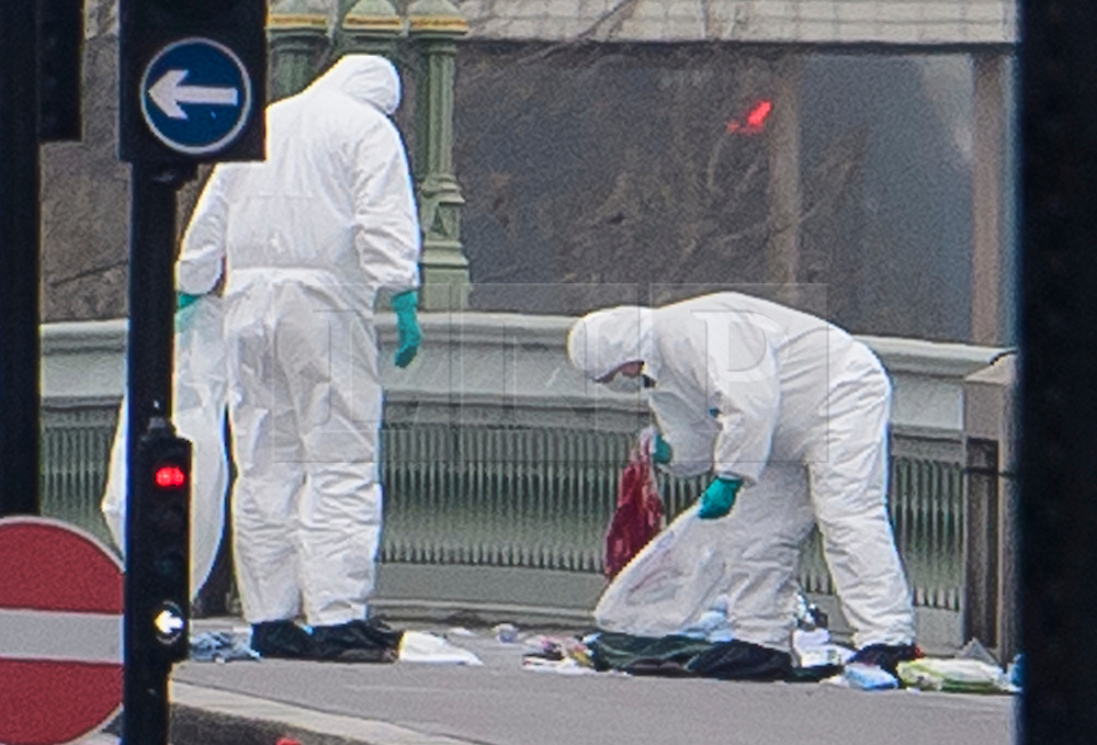 © Licensed to London News Pictures. 23/03/2017. London, UK. Police forensics collect personal belongings covered in blood from Westminster Bridge, where a car drove  in to the gates of the Houses of Parliament. Yesterday a lone terrorist killed 4 people and injured several more, in an attack using a car and a knife. The attacker managed to gain entry to the grounds of the Houses of Parliament, killing one police officer. Photo credit: Ben Cawthra/LNP
