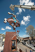 """Daniel Stewart of Yesco Signs maneuvers the """"bucking bronco"""" sign into place at the top of the Cowboy Bar on Tuesday. The sign returned to Jackson after several weeks in Boise, Idaho, for restoration."""