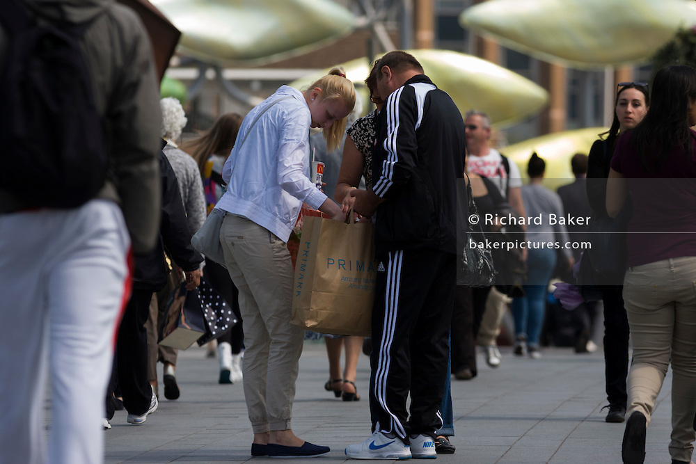 Shoppers pause on the busy walkway to Westfield's Stratford's mall, to check purchases from Primark.