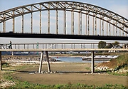 Nederland, Nijmegen, 19-10-2018 Drooggevallen bedding van een zijgeul van de Waal in de Ooijpolder. Door de lage waterstand is er geen aanvoer van water vanuit de rivier . Door het langdurg uitblijven van regen. droogte, is hij helemaal opgedroogd. In de achtergrond de vaargeul van de Waal.Foto: Flip Franssen