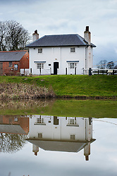 The Lock Keeper's Cottage reflected in the top pound, Foxton Locks, Grand Union Canal, Leicestershire, England, United Kingdom.