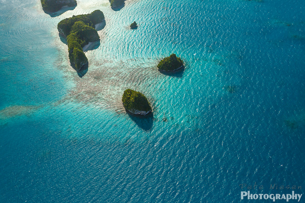 Aerial view of coral reefs, and tiny islands in the middle of the south pacific