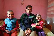 Liliana en 2014 avec deux de ses enfants dans la pièce où elle vit dans la maison de ses beaux-parents. Liliana est mère au foyer et son compagnon est un homme du village qui travaille dans le bâtiment en Allemagne. Depuis, Liliana a quitté son compagnon et est partie vivre avec ses enfants et un autre homme dans la région de Cluj Napoca. <br /> <br /> Liliana in 2014 with two of her children at her in-laws'. In 2018 she left with her children to live with another man near Cluj Napoca in Transylvania. <br /> <br /> Popricani, 2014