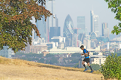 ©Licensed to London News Pictures 08/08/2020   Greenwich, UK. This runner enjoying the morning sun with a backdrop of the Gherkin in London. The warm weather continues today with early risers getting out and about in Greenwich Park, Greenwich, London. Photo credit: Grant Falvey/LNP