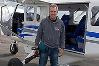 Photographer Mark Carwardine with plane used for aerial photography, Akureyri, Iceland