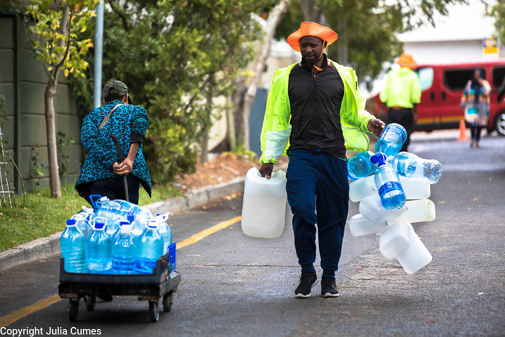As with any crisis, creative entrepreneurs have found ways of making some income from the Cape Town's water crisis. Here, enterprising workers, for a fee, offer to transport heavy water containers from a public spring on Spring Road to residents' waiting cars.