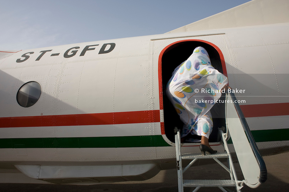 A lady attending the first international Conference on Womens' Challenge in Darfur, boards a chartered Russian Antonov aircraft during flight to Al Fasher (also spelled, Al-Fashir) where women from remote parts of Sudan gathered to discuss peace and political issues.